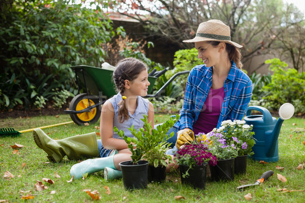 Smiling mother and daughter sitting with various potted plants Stock photo © wavebreak_media
