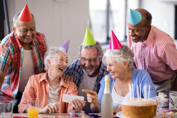 Vrolijk senior vrouw tonen mobiele telefoon vrienden Stockfoto © wavebreak_media
