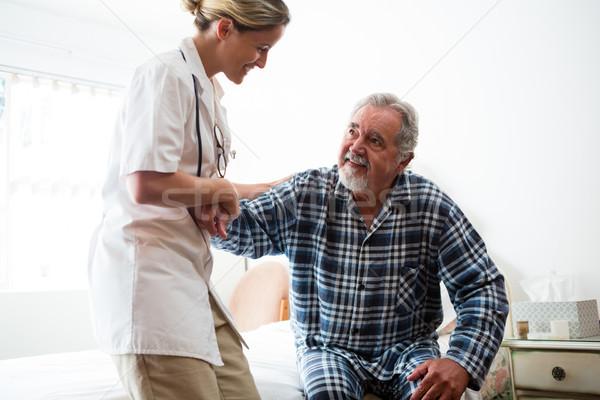 Female doctor assisting senior man in sitting on bed Stock photo © wavebreak_media