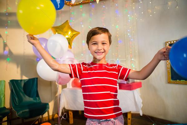 Happy boy holding balloons during birthday party Stock photo © wavebreak_media
