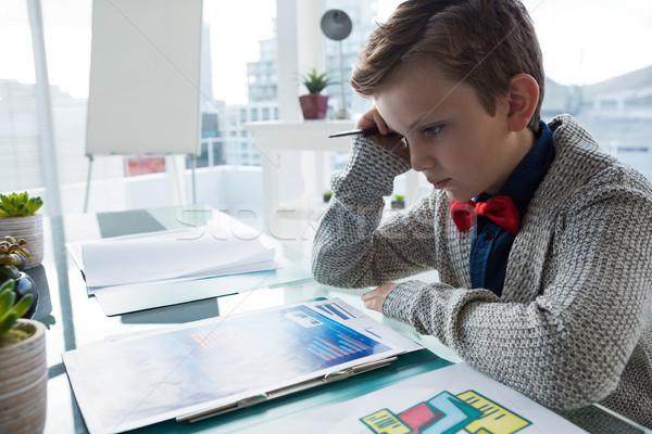 Close up of businessman reading documents while sitting at desk Stock photo © wavebreak_media
