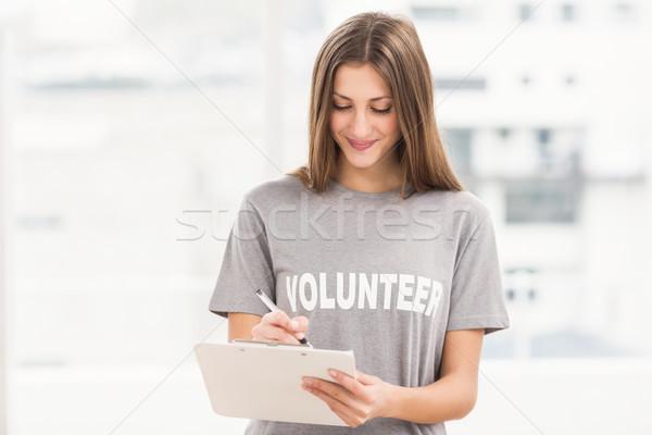 Sorridente morena voluntário escrita clipboard escritório Foto stock © wavebreak_media
