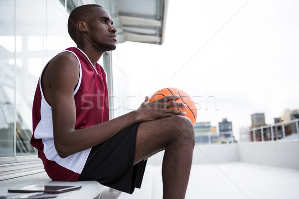 Thoughtful player holding basketball Stock photo © wavebreak_media