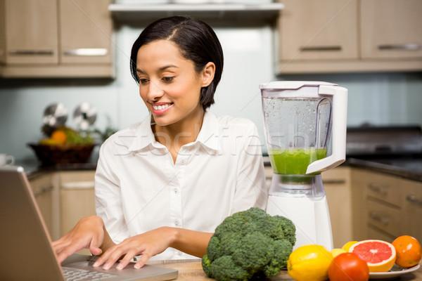 Mosolyog barna hajú laptopot használ smoothie konyha boldog Stock fotó © wavebreak_media