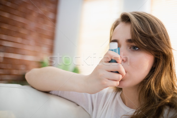 Woman using her inhaler on couch Stock photo © wavebreak_media