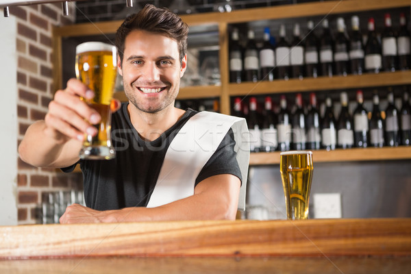 Handsome barman holding a pint of beer Stock photo © wavebreak_media