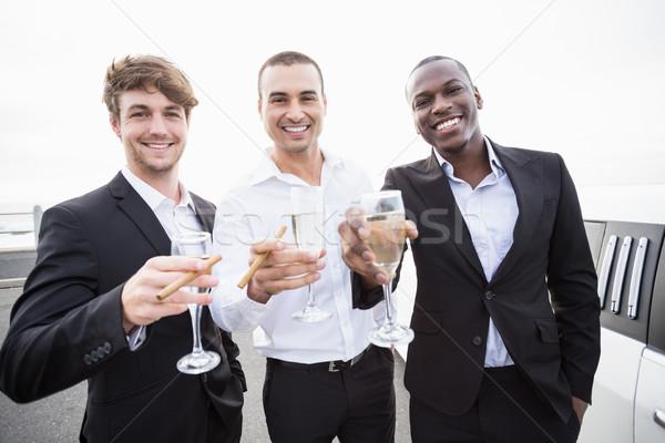 Jólöltözött férfiak iszik pezsgő limuzin bulizás Stock fotó © wavebreak_media