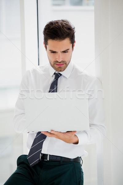 Affaires utilisant un ordinateur portable prendre des notes bureau papier homme Photo stock © wavebreak_media