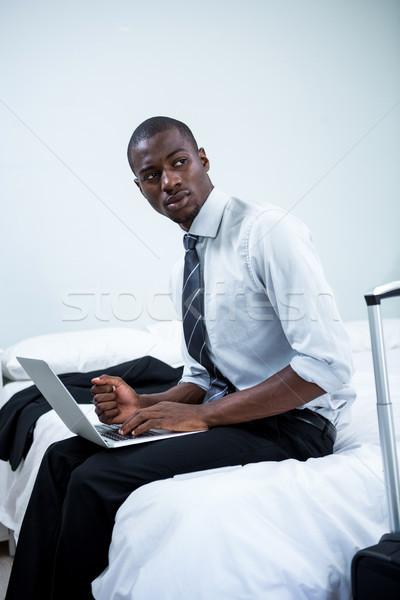 Jonge man vergadering bed met behulp van laptop slaapkamer computer Stockfoto © wavebreak_media