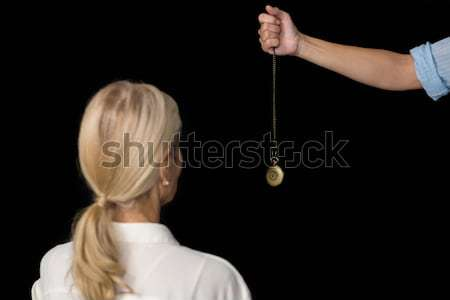 Cropped image of hypnotherapist holding pendulum by woman Stock photo © wavebreak_media