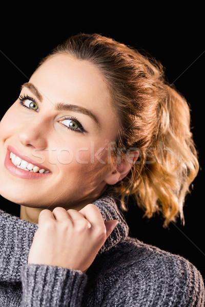 Portrait of beautiful woman posing against black background Stock photo © wavebreak_media