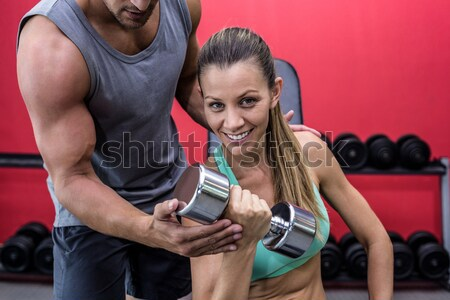 Portrait of smiling man lifting dumbbell in gym Stock photo © wavebreak_media
