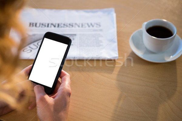 Stock photo: Woman using her mobile phone with newspaper and coffee cup on table