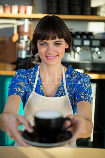Retrato camarera ofrecimiento taza café sonriendo Foto stock © wavebreak_media