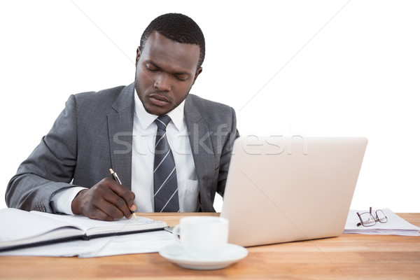 Concentrated businessman working at office desk Stock photo © wavebreak_media