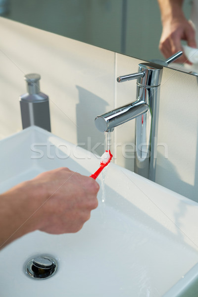 Man washing his toothbrush under sink in bathroom Stock photo © wavebreak_media