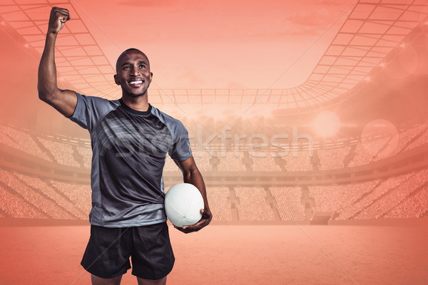 Composite image of happy sportsman with clenched fist holding ru Stock photo © wavebreak_media