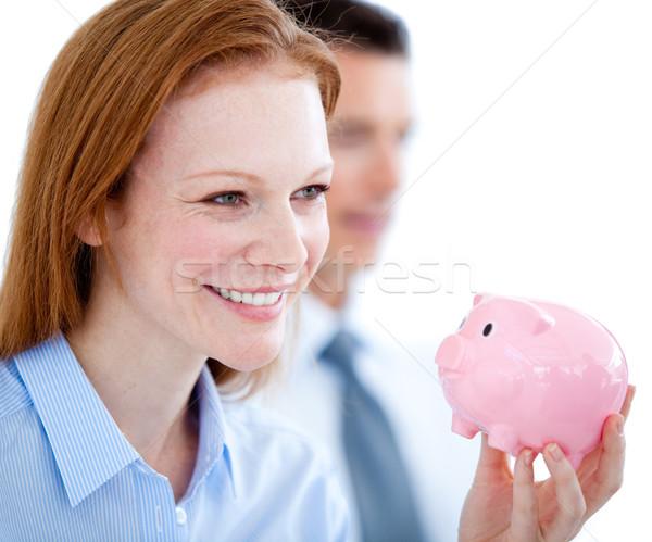 Smiling businesswoman holding a piggybank Stock photo © wavebreak_media
