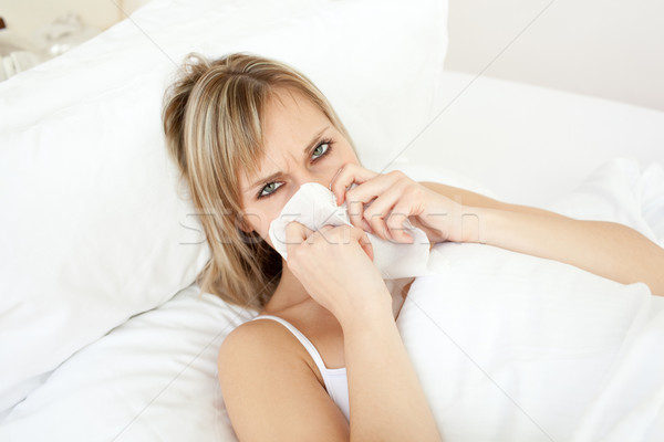 Sick blond woman blowing lying on her bed  Stock photo © wavebreak_media