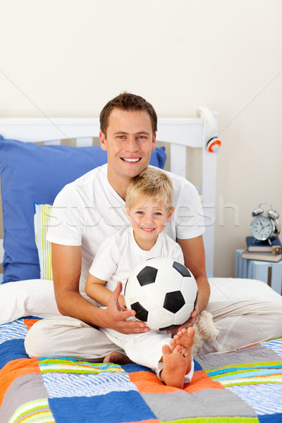 Portrait of a little boy and his father playing with a soccer ba Stock photo © wavebreak_media