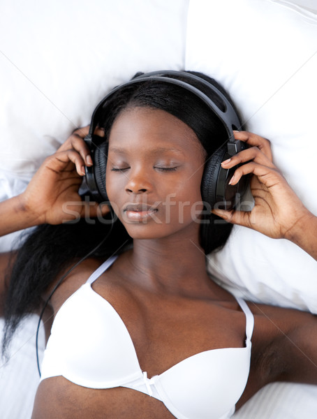 Radiant woman listening music lying on her bed Stock photo © wavebreak_media