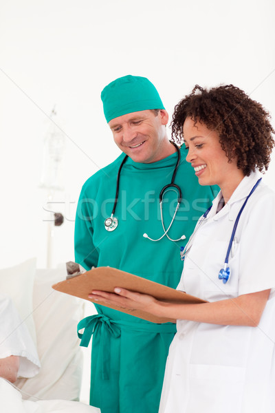 Nice female doctor with surgeon holding a paper  Stock photo © wavebreak_media