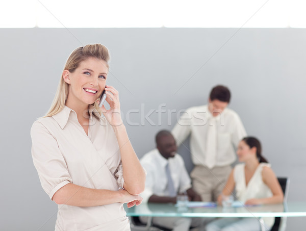 Smiling female talking on the phone with her team in a office Stock photo © wavebreak_media