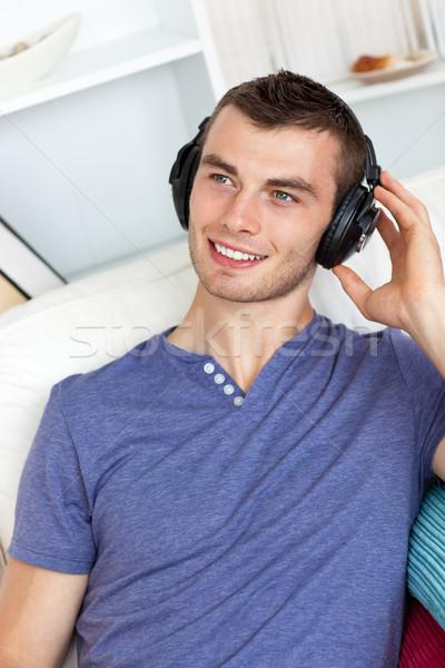 Good-looking man listening to music in living room Stock photo © wavebreak_media