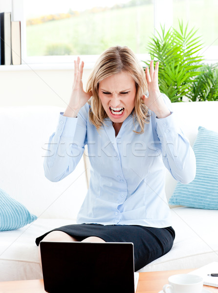 Young businesswoman sitting on her sofa getting frustrated with her laptop at home Stock photo © wavebreak_media