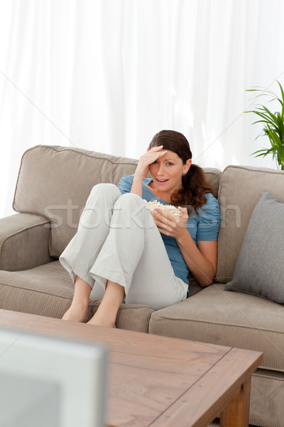 Beautiful woman watching a horror movie on television at home Stock photo © wavebreak_media