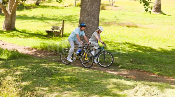 Aposentados casal mountain bike fora grama verão Foto stock © wavebreak_media