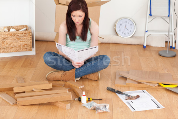 Good looking red-haired girl reading a manual before do-it-yourself at home Stock photo © wavebreak_media