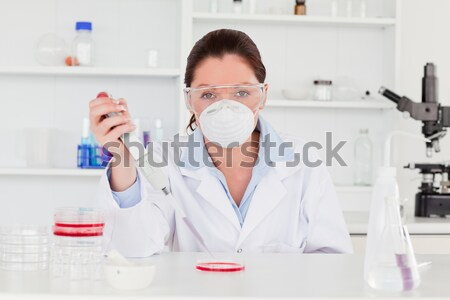 Attractive female biologist holding a manual pipette with sample from test tubes in a lab Stock photo © wavebreak_media