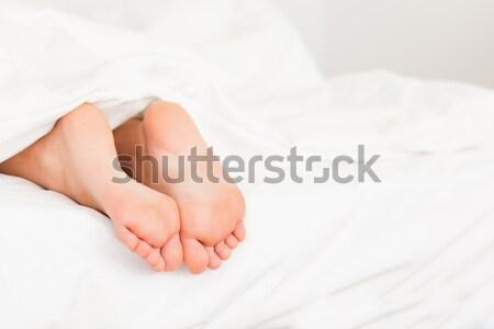Portrait of four feet in a bed Stock photo © wavebreak_media