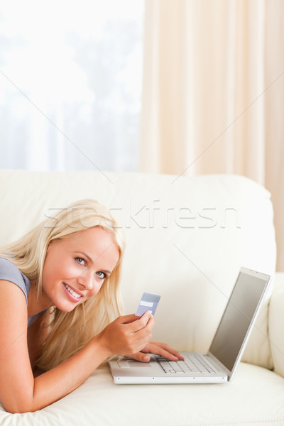 Portrait of a smiling woman purchasing online in her living room Stock photo © wavebreak_media