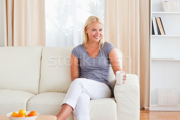 Donna seduta divano Cup tè soggiorno Foto d'archivio © wavebreak_media