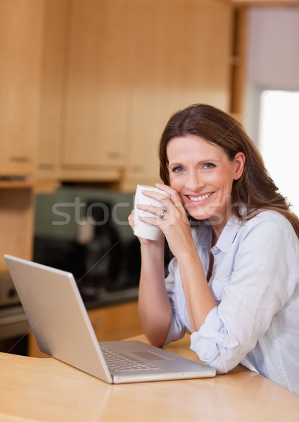 Stock photo: Smiling woman with cup next to laptop