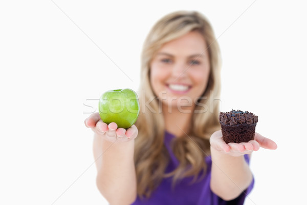 A fruit and a muffin being held by a blonde woman against a white background Stock photo © wavebreak_media