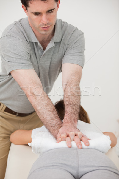 Woman lying forward while a physiotherapist massaging her back in a room Stock photo © wavebreak_media