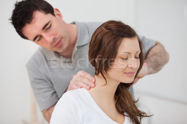 Smiling woman sitting while being massaged by a man in a room Stock photo © wavebreak_media