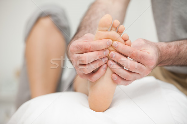 Stock photo: Sole of a foot being touched by a doctor in a room