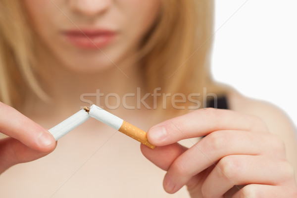 Serious woman breaking a cigarette against white background Stock photo © wavebreak_media