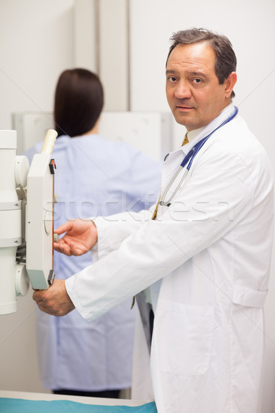 Doctor checking a machine while a patient is having a mammography in an examination room Stock photo © wavebreak_media