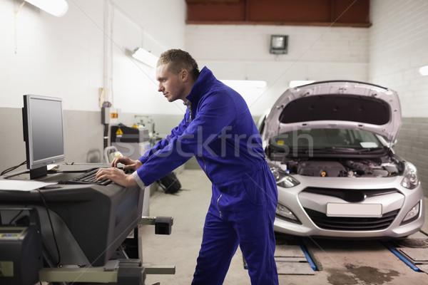 Mechanic using a computer in a garage Stock photo © wavebreak_media