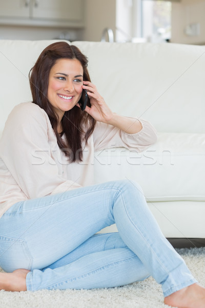 Woman smiling while calling and sitting on the carpet Stock photo © wavebreak_media