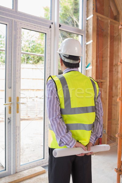 Architect wearing a warning vest and a helmet looking out of the window Stock photo © wavebreak_media