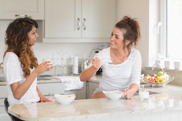 Duas mulheres alimentação cereal cozinha diversão Foto stock © wavebreak_media