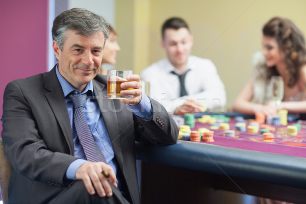 Homme potable whiskey roulette table casino Photo stock © wavebreak_media