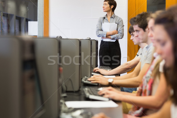 Concentrate students sitting at the computer room while teacher standing at top of class in college  Stock photo © wavebreak_media