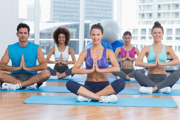 People in Namaste position smiling at fitness studio Stock photo © wavebreak_media